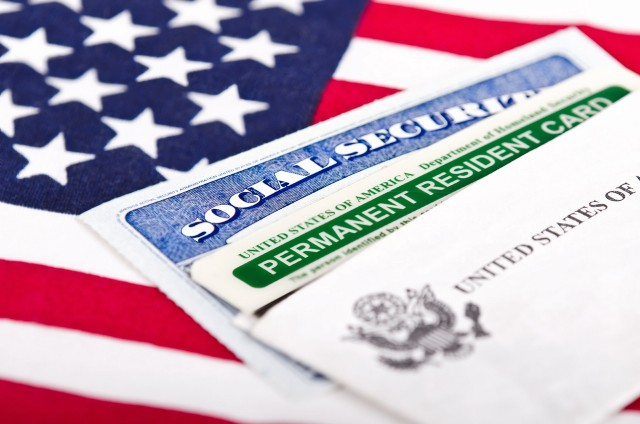 Social security card and green card on an American flag