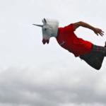 Man in unicorn mask, jumping