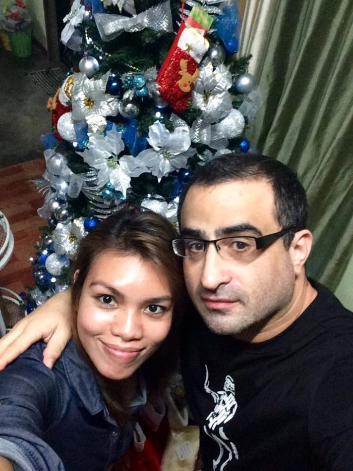 Adam and Charmay in front of their Christmas tree, December 2016