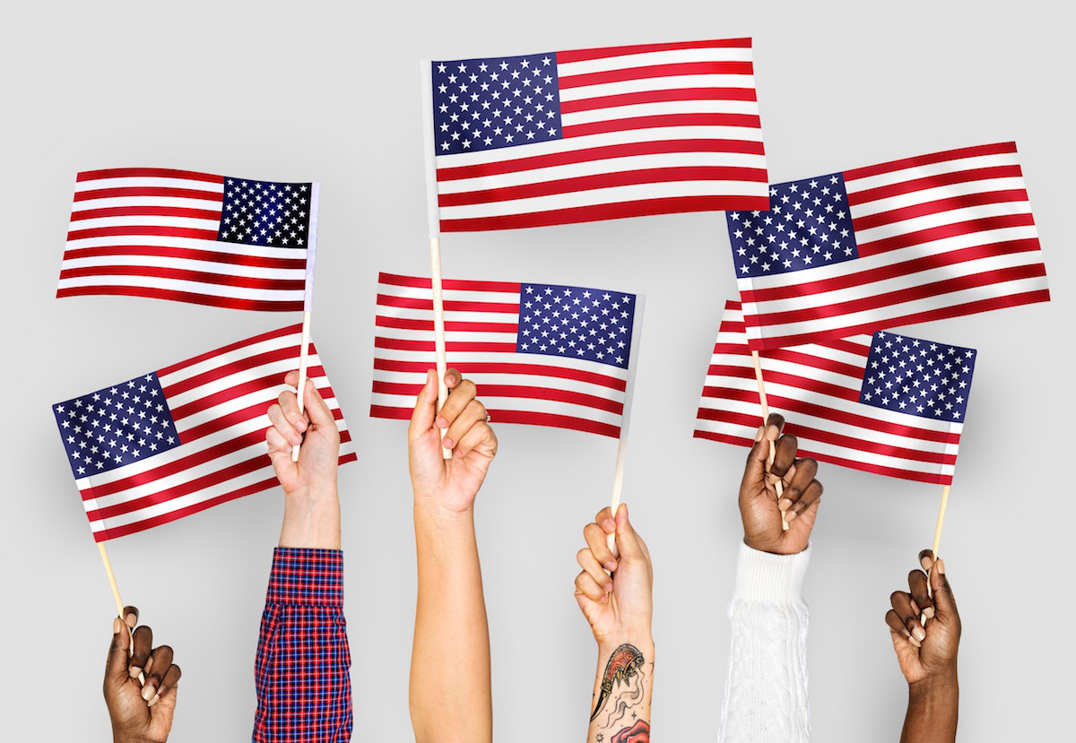 Hands of American Citizens Raising US Flags