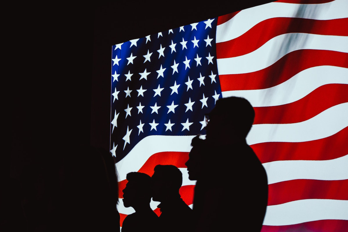 Silhouettes of New US Citizens Against US Flag
